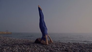 Young woman in bodysuit practicing yoga on the beach above sea at amazing sunrise. Fitness, sport, yoga and healthy lifestyle concept. Girl doing complicated yoga asana