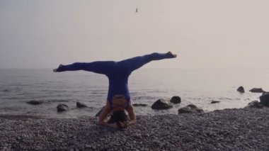 Young woman in bodysuit practicing yoga on the beach above sea at amazing sunrise. Fitness, sport, yoga and healthy lifestyle concept. Girl doing stand on head and twine