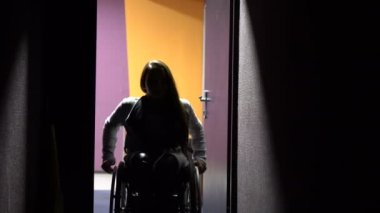 The girl on a wheelchair coming in the cinema. Disabled leisure