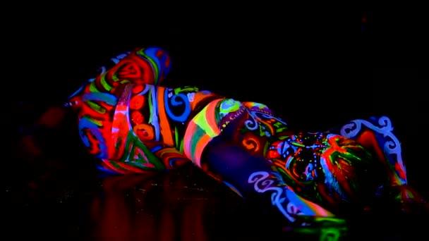Szép fiatal szexi lány fehérnemű tánc ultraibolya festék a testén. A színes fény neon bodyart lány.