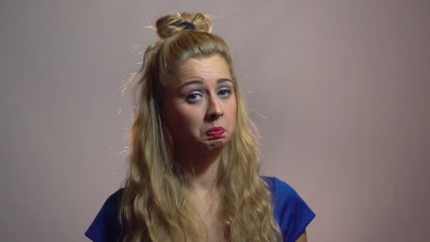 Krásná Sexy blondýnka dívka v modrých šatech je zobrazeno palce na vás ve studiu s osvětlením pozadí