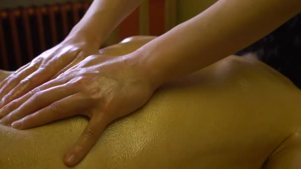 Masseur Woman Makes Massage Of Back With Warm Oil To A Young Man Stock Video