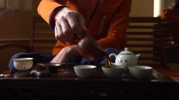 Muž, nalil Puer čaje v konvici na tradiční čínský čajový obřad. Sada zařízení pro pití čaje