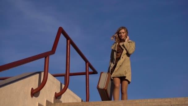 attraktive junge blonde Frau in Trenchcoat und Stöckelschuhen mit Vintage-Koffer geht die Treppe hinunter zur Seebrücke