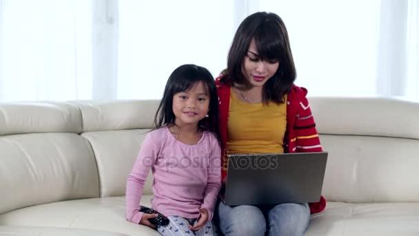 Žena a dcera s notebookem na pohovce