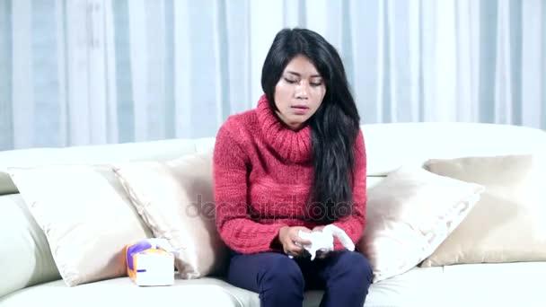Mladá žena kýchání na pohovce