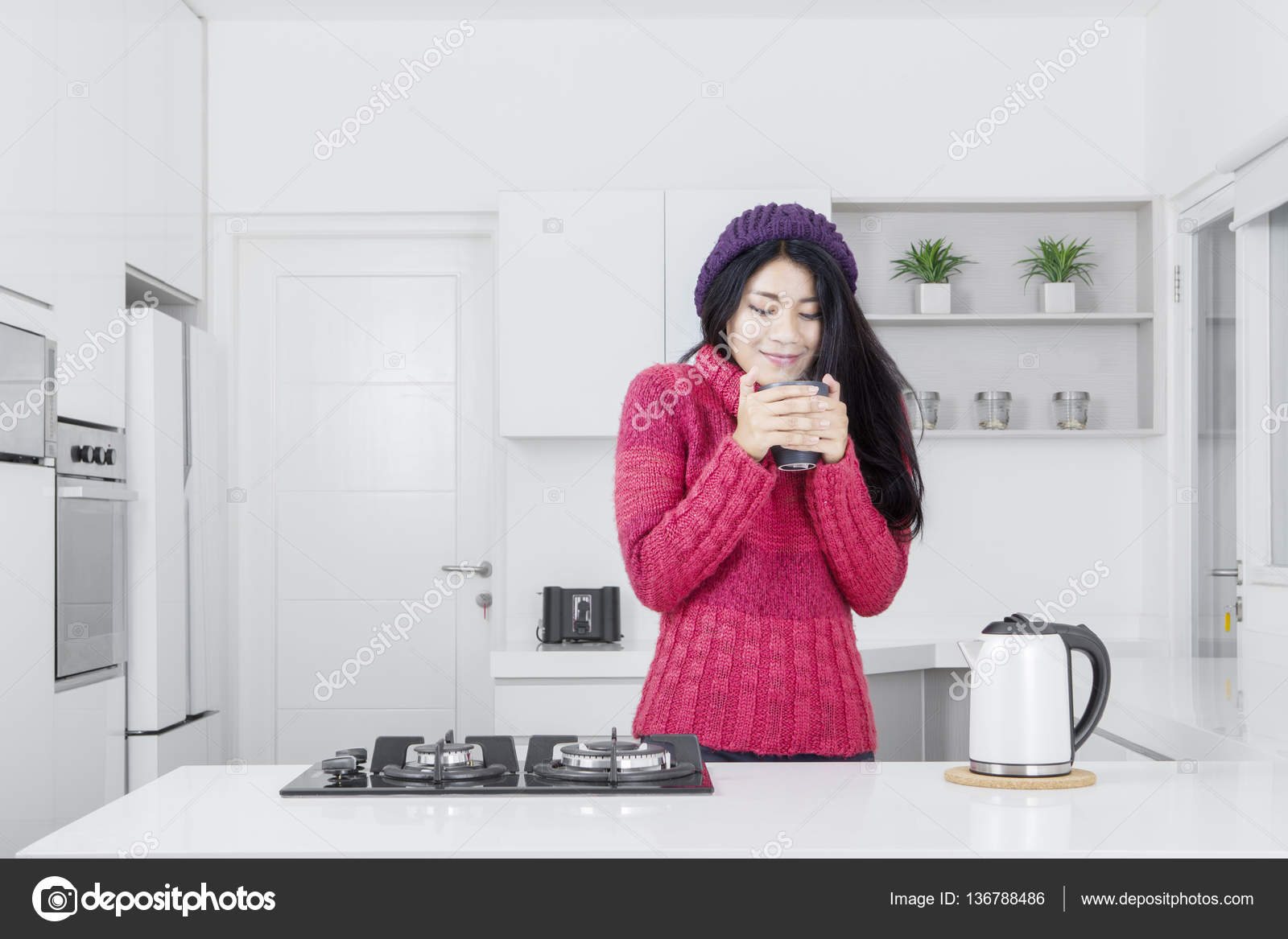 Young woman with hot drink in kitchen — Stock Photo © realinemedia ...