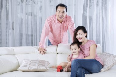 Happy smiles Asian family on the couch