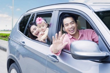 Happy family looking out car window