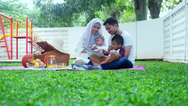Muslim family use digital tablet at park