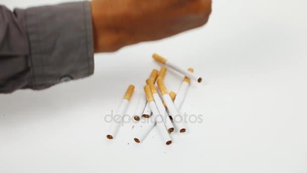 Hand zerbricht Zigaretten mit der Faust