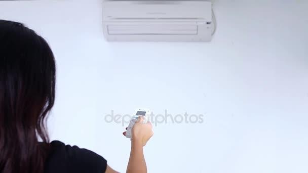 Frau schaltet Klimaanlage ein