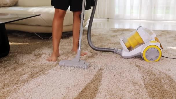 Frau saugt Teppich ab