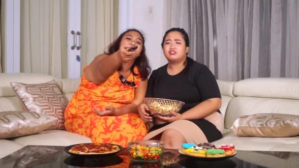 Obézní ženy jíst nezdravé potraviny na pohovce