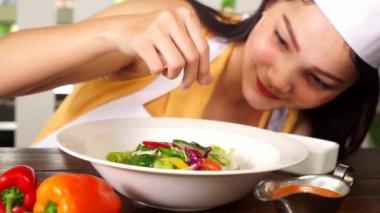 Chef sprinkling salt into vegetable salad