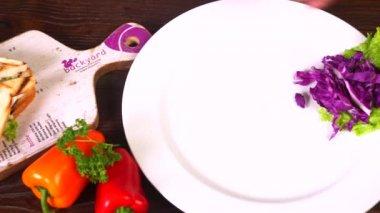 Hands preparing sandwich on plate