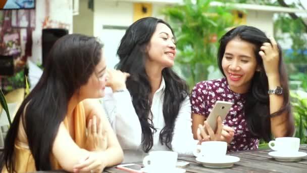 Tři krásné ženy pomocí smartphone v kavárně