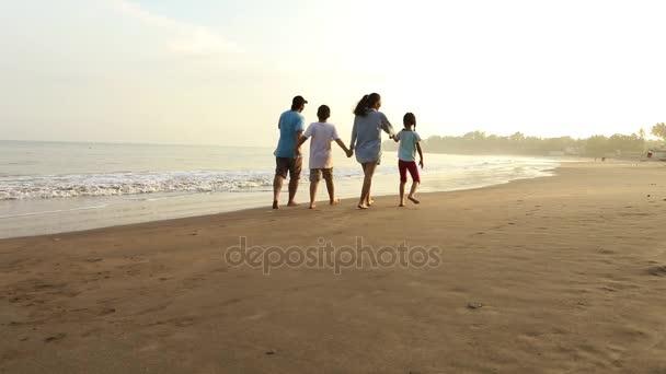 Happy family walk on sandy beach