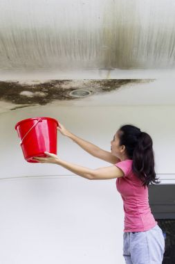 Asian woman with bucket and damaged ceiling