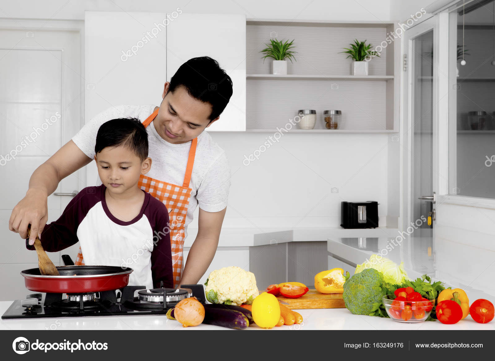 Young father teaches his son to cook — Stock Photo © realinemedia ...