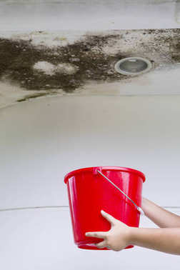 Woman with a bucket under damaged ceiling