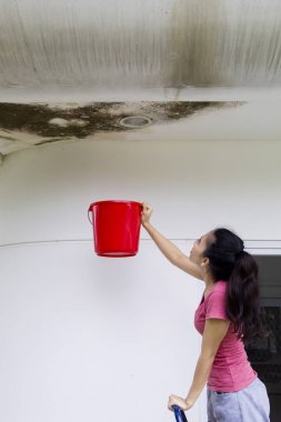 Young woman collecting rainwater with a bucket