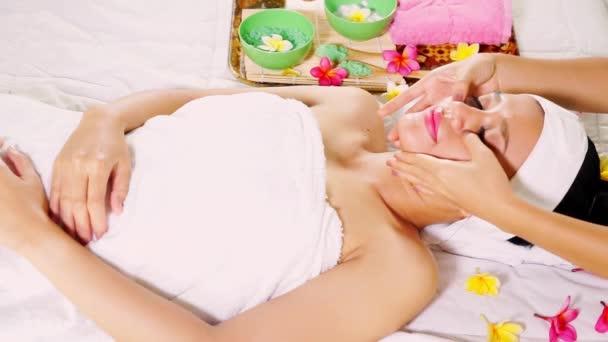 Žena se těší masáž obličeje v kosmetickém salonu