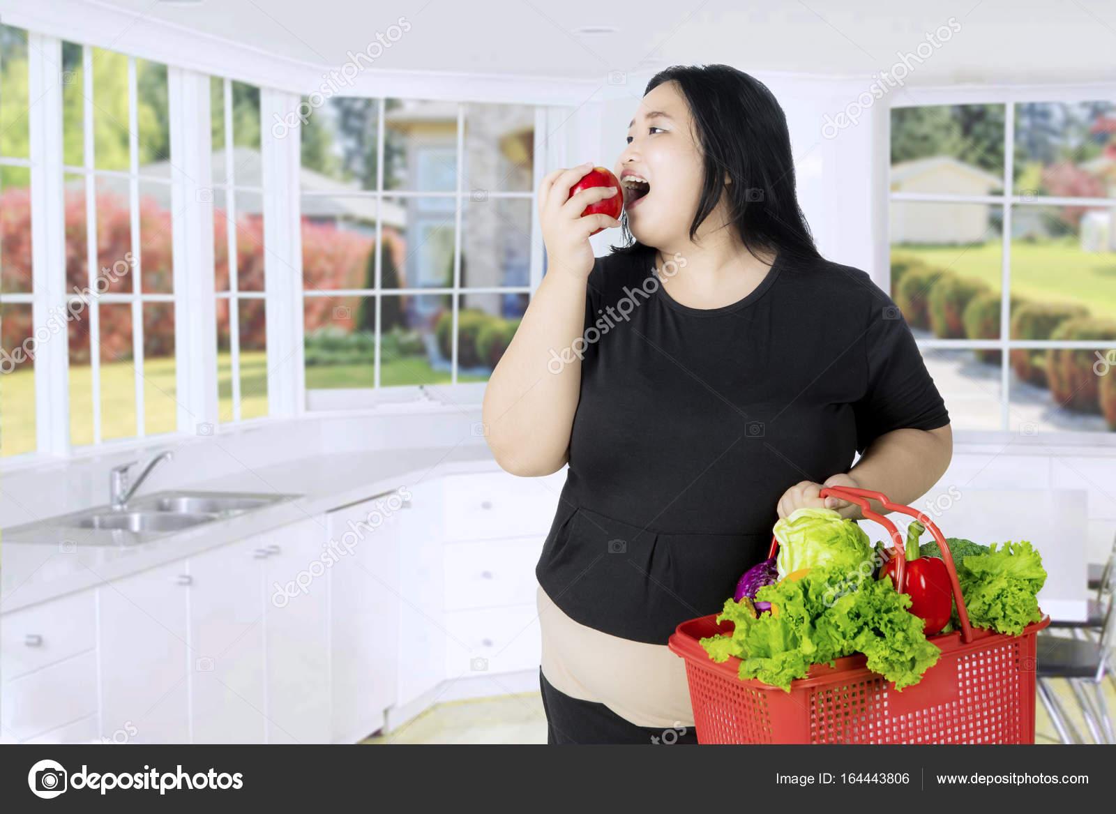 Übergewichtige Frau in der Küche einen Apfel essen — Stockfoto ...