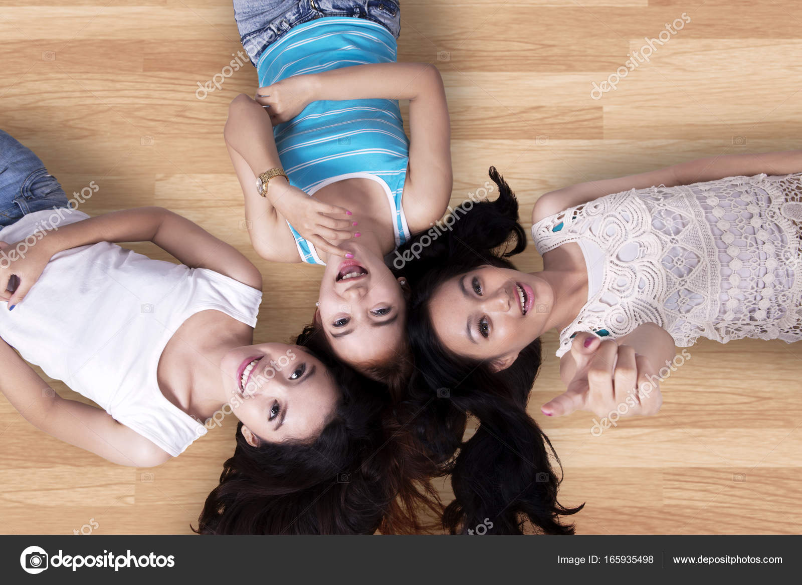 Pretty Girls Lying Down On The Wooden Floor Stock Photo