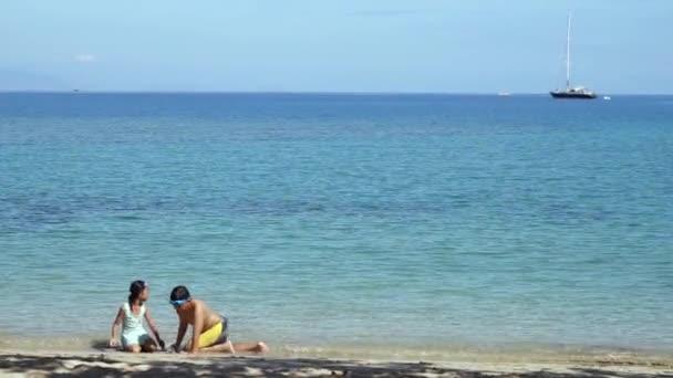 Šťastné děti hrají písek na pláži