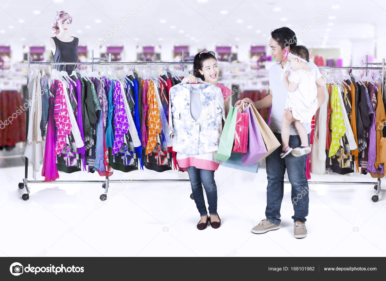 6cb2269b0 Family trying clothes in clothing store — Stock Photo © realinemedia ...