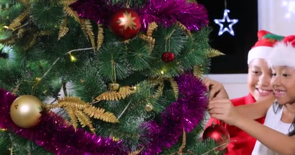 Zwei Kinder schmücken Weihnachtsbaum