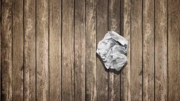 Zmačkaný papír míč na dřevěný stůl
