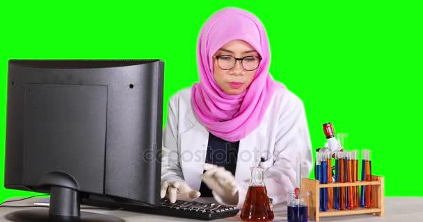 Vědec, který pracuje s počítačem a zkumavky
