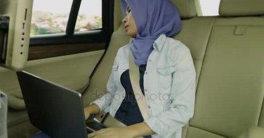 Muslim woman sleeping in car with laptop