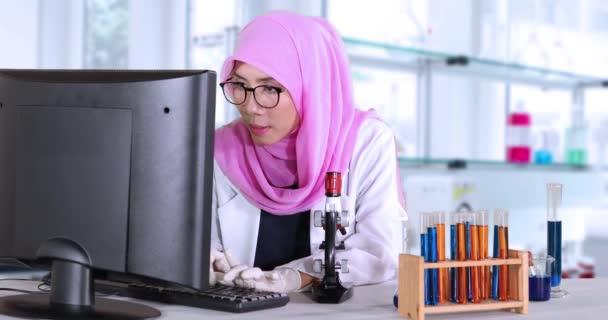 Vědec s počítačem a mikroskopem v laboratoři