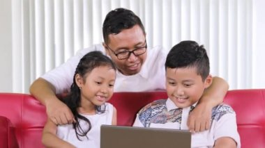 Young father protecting his kids from inappropriate content on the laptop by closing their eyes in the living room at home