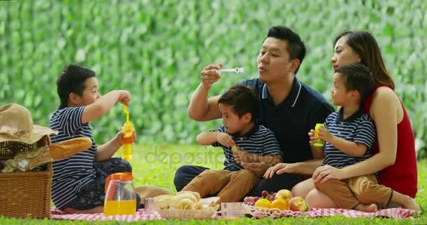 Asijská rodina s manželských dětí sedí v parku při hraní mýdlové bubliny a pikniky. Snímek v rozlišení 4 k