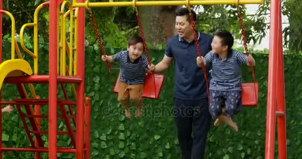 Dvě šťastné děti si hrají na houpačce se svým otcem v parku. Snímek v rozlišení 4 k