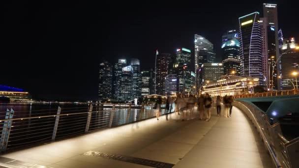 Singapur - 27 listopadu 2017: Časosběrné záběry ze Singapuru centra v noci s výhledem na mrakodrapy a chodců na mostě Esplanade. Snímek v rozlišení 4 k