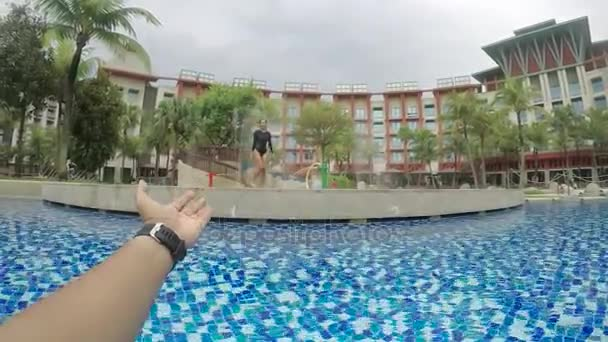 Video footage of a male hand invites his girlfriend to swim on the luxury hotel pool