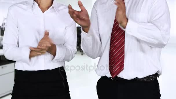 Video footage of two unknown businesspeople clapping hands together while standing in office