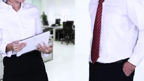 Video footage of two anonymous businesspeople shaking hands and discussing together with a digital tablet in the office room