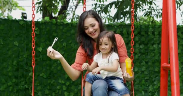 Happy young woman and her daughter having fun together while blowing soap bubbles and sitting on the swing at the park, shot in 4k resolution