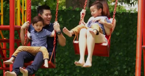 Happy Asian parents with twin children enjoying leisure time while having fun together on swing at the park, shot in 4k resolution