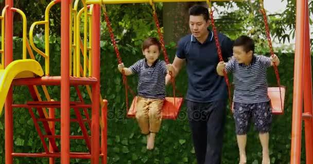 Dvě šťastné děti a jejich otec, využití volného času při hraní na houpačce v parku, zastřelil v rozlišení 4 k