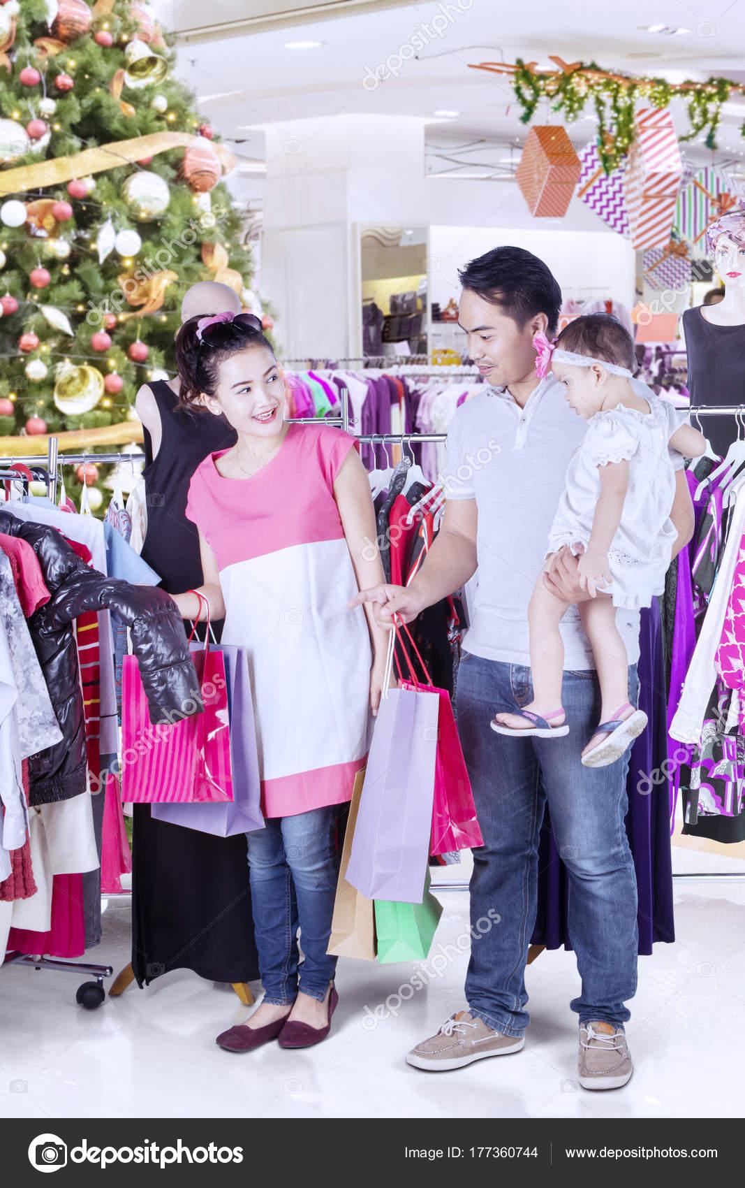 422b54f8a4c1 Νεαρή οικογένεια επιλέγουν ρούχα στο πολυκατάστημα — Φωτογραφία Αρχείου