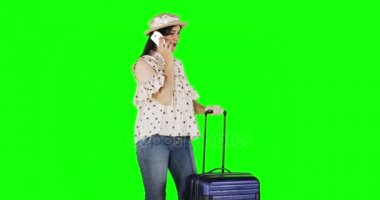 Pretty female traveler talking on mobile phone while holding her suitcase in front of green screen background, shot in 4k resolution