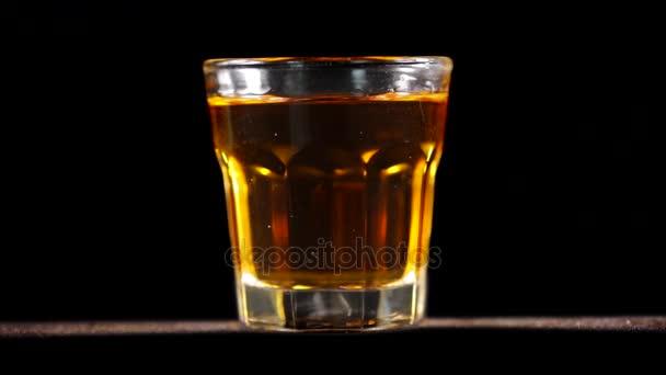 Vértes egy whiskys pohár az asztalon, a sötét háttér spinning