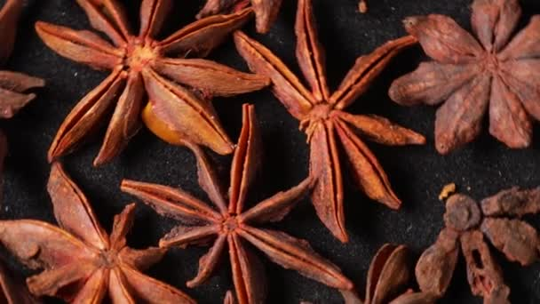 Top view footage of star anise seeds rotate on the black table. Oriental cuisine ingredients concept
